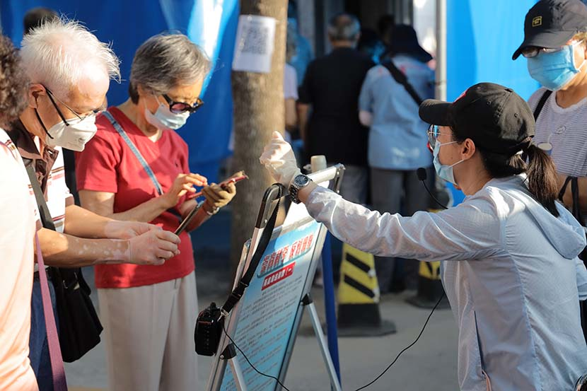 Elderly people scan a QR code to book a reservation to visit a public park in Beijing, July 6, 2020. People Visual