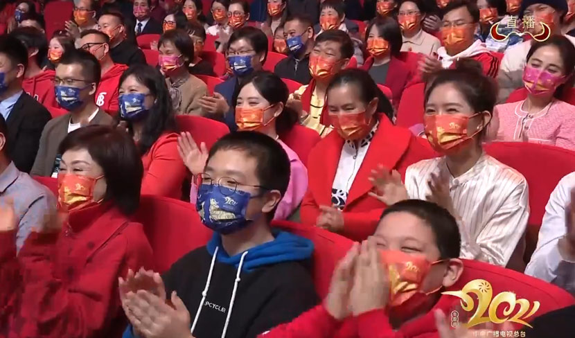 Audience members wearing ox-themed face masks applaud during the 2021 Spring Festival Gala. From @春晚 on Weibo