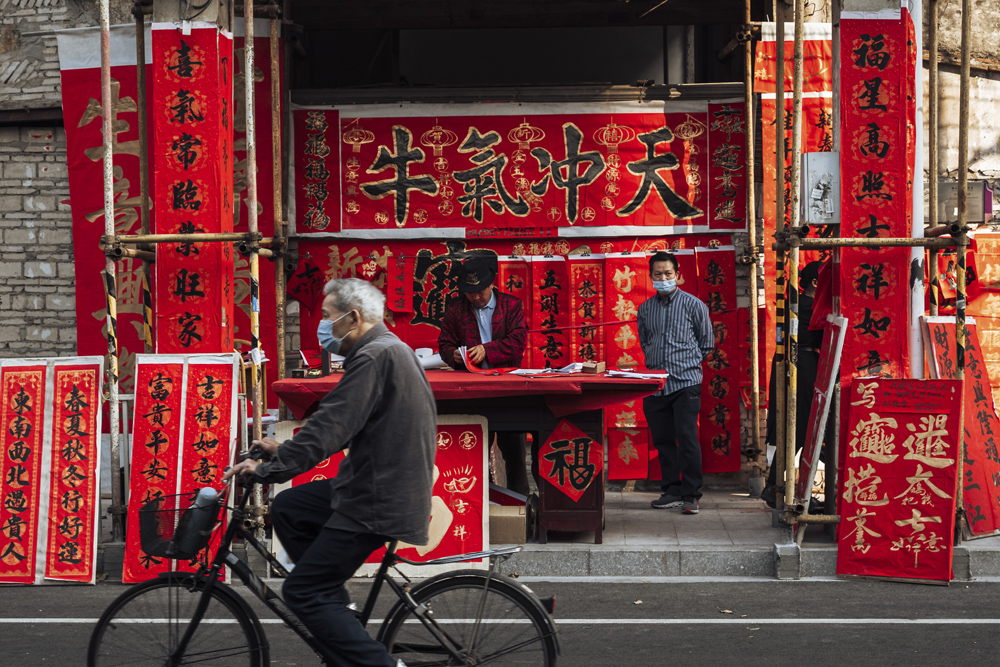An elderly man rides past a booth selling spring couplets in Foshan, Guangdong province, Feb. 6, 2021. Long Yilin/People Visual