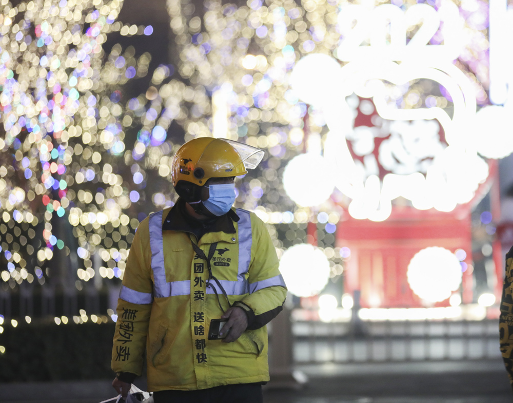 A delivery man works on the first day of the lunar year in Beijing, Feb. 12, 2021. Many migrant workers chose to stay put in the cities this Lunar New Year holiday. Jiang Qiming/CNS/IC