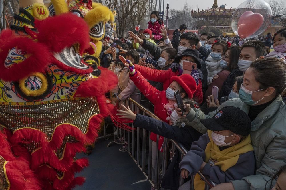 People wearing face masks reach towards a team performing a traditional lion dance to mark the first day of the Lunar New Year at a park in Beijing, Feb. 12, 2021. Kevin Frayer/Getty Images/People Visual