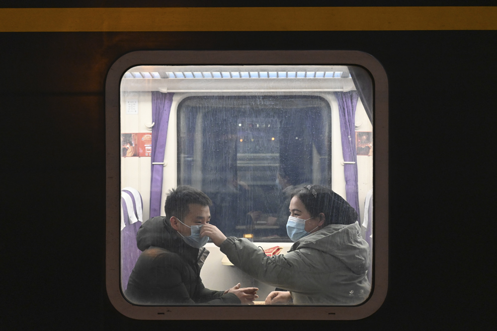 A woman helps her husband put on a face mask properly on a homeward-bound train at a railway station in Shijiazhuang, Hebei province, Feb. 11, 2021. Zhai Yujia/CNS/People Visual