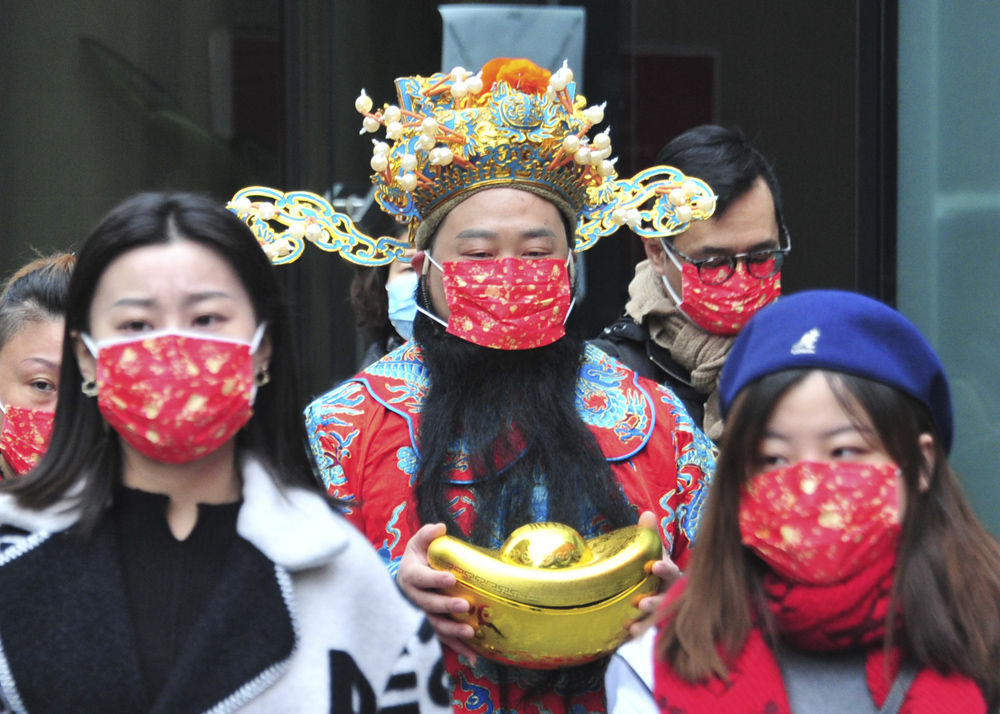 A man in a god of wealth costume wears a holiday-themed face mask in Shanghai, Feb. 15, 2021. Yang Jianzheng/People Visual