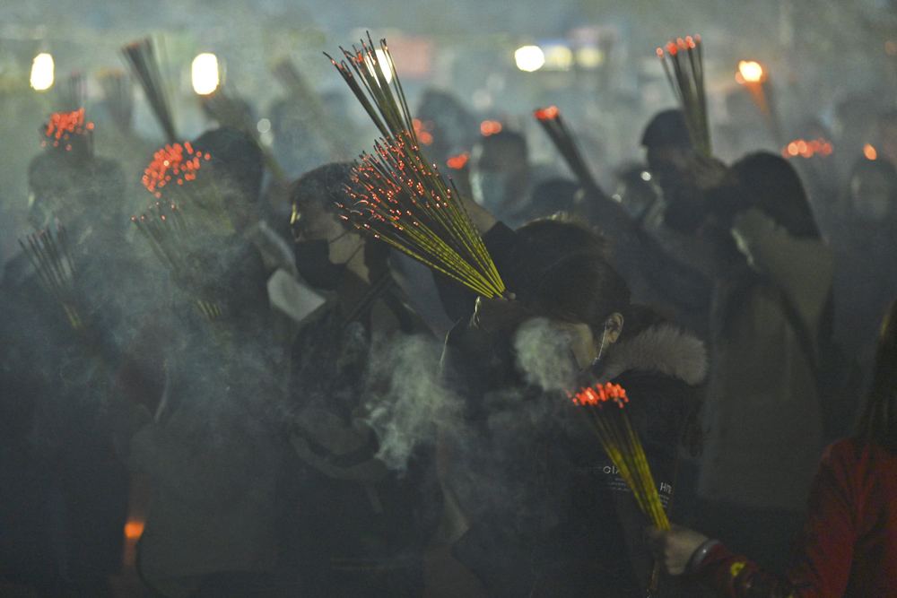 People pray and burn joss sticks piously at a temple on the eve of the Lunar New Year in Nanning, Guangxi Zhuang Autonomous Region, Feb. 11, 2021. People Visual