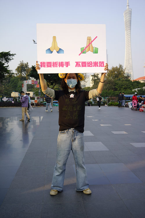 An artist holding a poster showing old (left) and new WeChat emojis poses for a photo in Guangzhou, Guangdong province, Jan. 30, 2021. Courtesy of Wang Huadong