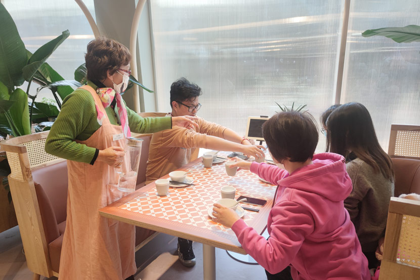 An elderly staff member serves tea at the Forget-Me-Not Café in Shanghai, Feb. 24, 2021. Zhang Chaoyan for Sixth Tone
