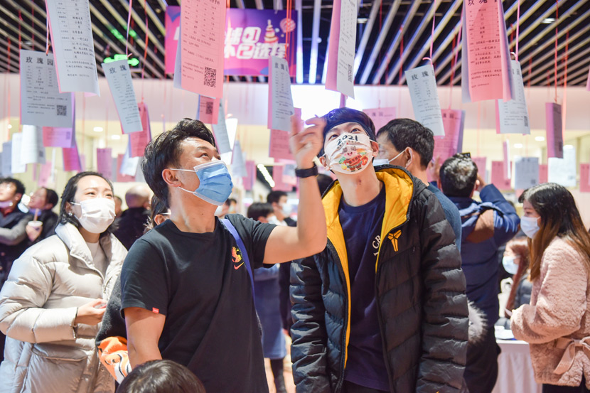 Young people check the information of other attendees at a dating event in Yiwu, Zhejiang province, Feb. 14, 2021. Mao Xuqian/People Visual