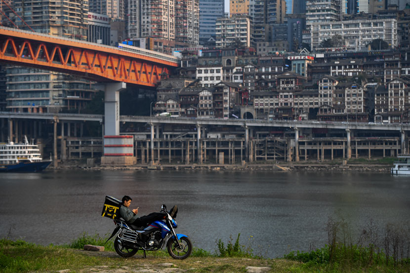 A delivery driver takes a break by the Jialing River in Chongqing, March 2020. Li Xiangbo/People Visual