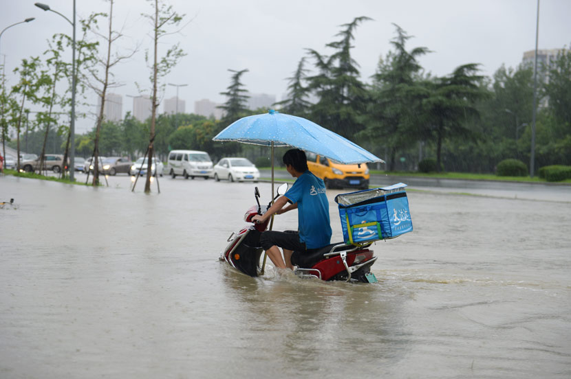 A delivery driver crosses a flooded street in Chengdu, Sichuan province, Aug. 11, 2020. Gao Han/People Visual