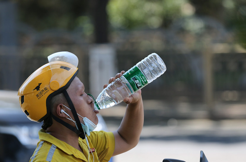 A delivery worker drinks water on a hot summer day in Beijing, July 2020. Yang Kejia/CNS/People Visual