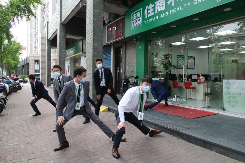 Real estate agents perform exercises outside an office in Shanghai, April 2020. Wang Rongjiang/People Visual