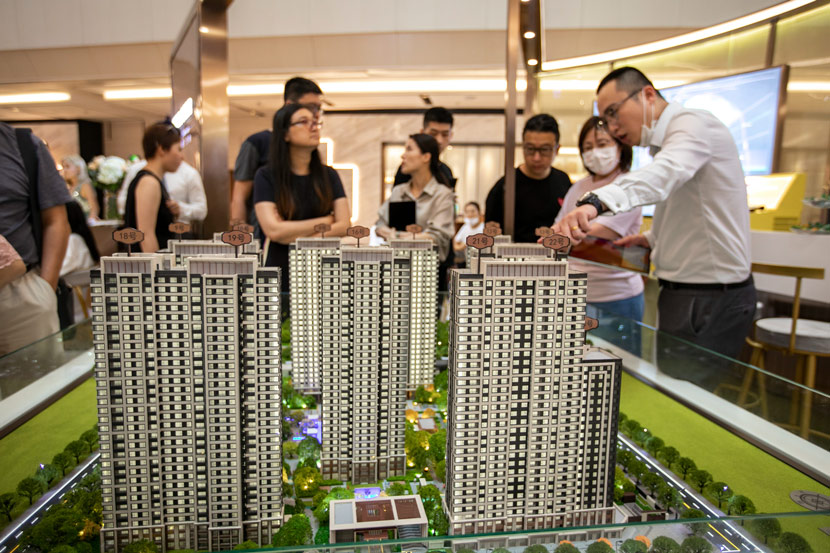A salesperson introduces a new development to potential buyers at a sales office in Shanghai, Aug. 1, 2020. Lü Liang/IC