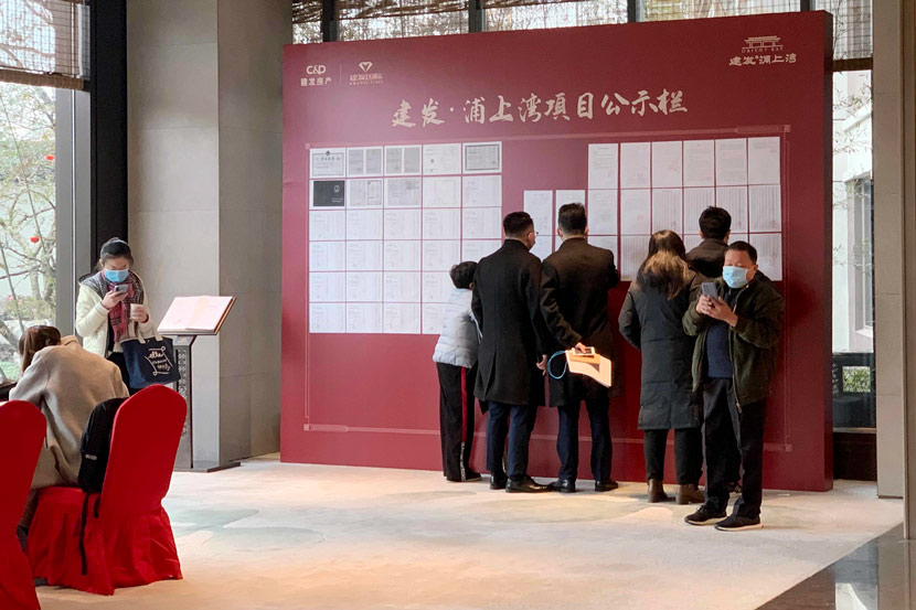 Consumers read bulletins posted in the sales office of a new real estate development in Shanghai, Feb. 6, 2021. Bai Kelin/IC