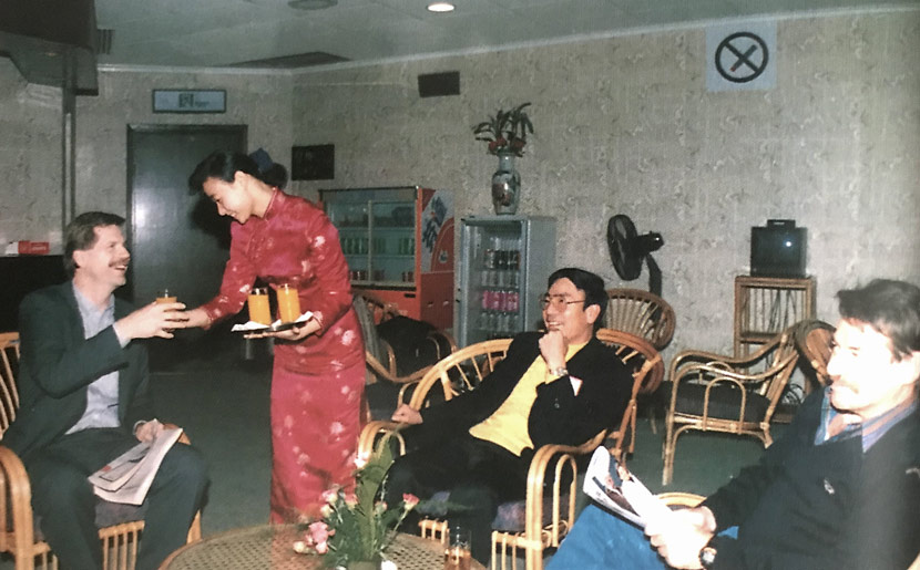 A ground service staff member serves drinks to passengers in a VIP room at Shanghai Hongqiao Airport, 1993. Courtesy of Luo Keping