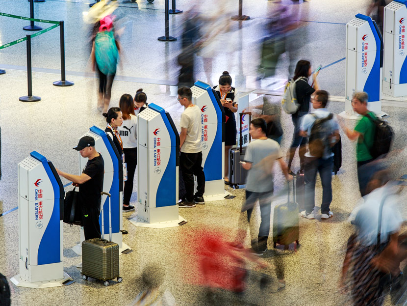 Passengers use electronic check-in stations at Shanghai Hongqiao Airport, May 18, 2018. People Visual