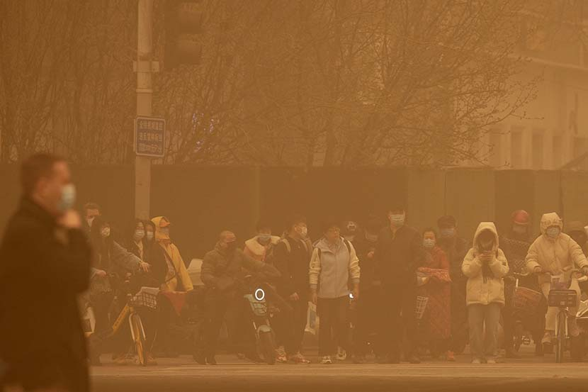 People wait to cross an intersection during the morning rush hour as a massive sandstorm engulfs Beijing, March 15, 2021. The sandstorm brought a tinted haze to Beijing's skies and sent air quality indices soaring. People Visual