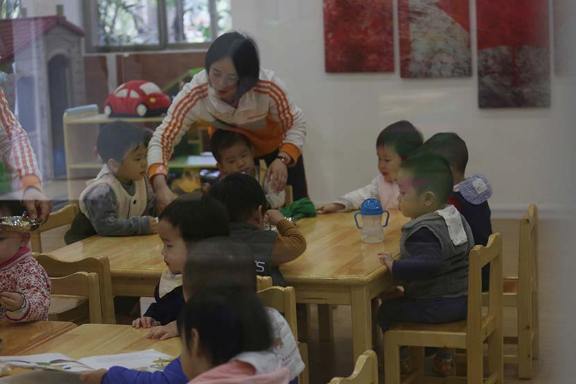 A teacher supervises children during lunchtime at a day care center in Guangzhou, Guangdong province, March 1, 2019. People Visual