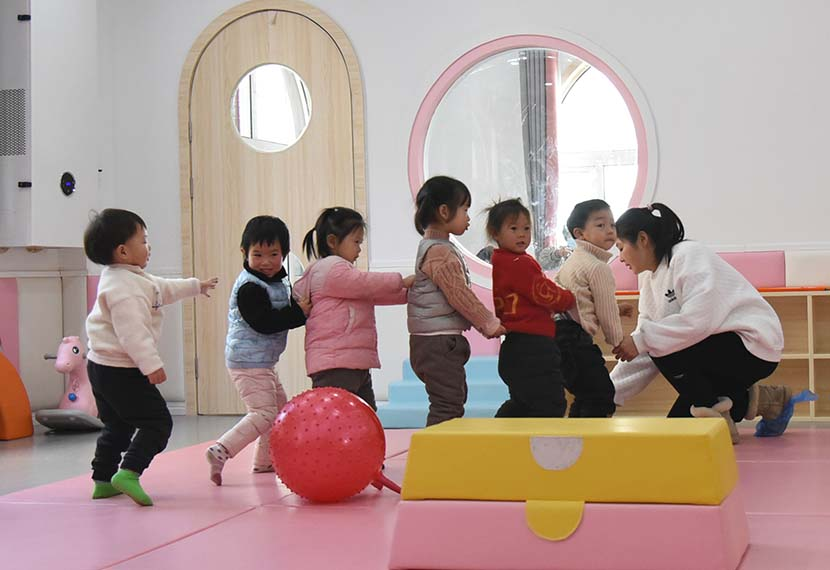 A teacher leads a game for her class at a day care center in Lianyungang, Jiangsu province, Jan. 15, 2021. People Visual