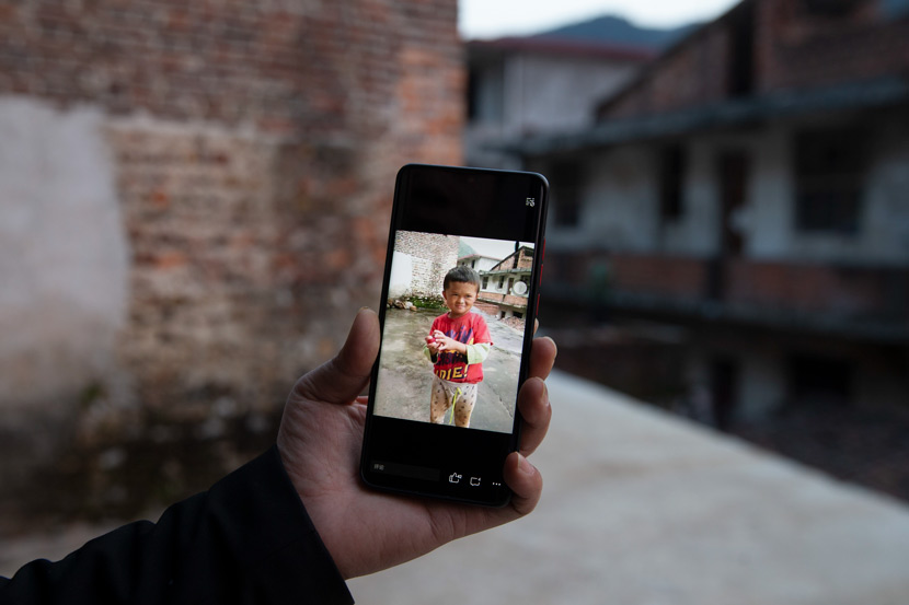 Huang Xinlong, Fan Xiaoqin's cousin, shows a photo of Xiaoqin on his phone, in Yanhui Village, Ji'an, Jiangxi province, Feb. 22, 2021. Huang created the social post about Xiaoqin's resemblance to Jack Ma that went viral in 2015. IC
