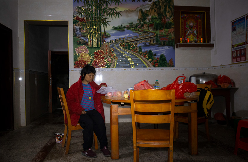 Fan Xiaoqin's mother sits in the living room of her family home in Yanhui Village, Ji'an, Jiangxi province, Feb. 22, 2021. IC