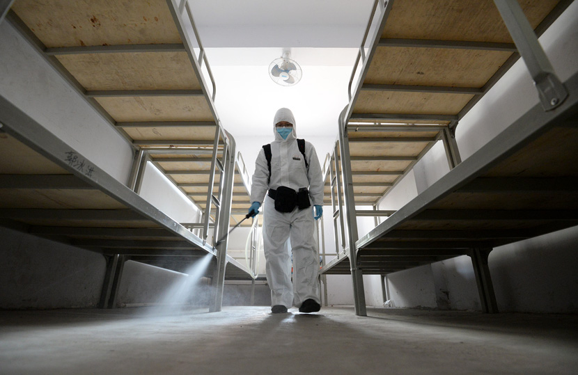 A worker sprays disinfectant inside a student dormitory in Handan, Hebei province, Feb. 26, 2021. Hao Qunying/People Visual