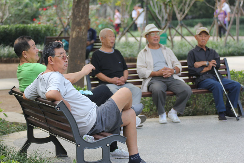 Middle-aged and elderly men sit in a park in Qingdao, Shandong province, 2016. People Visual