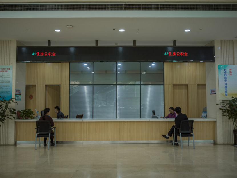 """A divorced couple meet at a local housing bureau to transfer the ownership of their house to their daughter, in a photograph from the series """"When We Two Parted,"""" 2019. The couple had recently finalized their divorce. Courtesy of Gao Meilin"""
