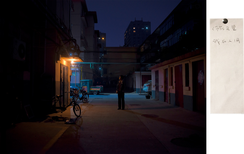 """A woman stands outside her old apartment, in a photograph from the series """"When We Two Parted,"""" 2019. The woman's ex-husband died following their separation. The note she wrote to him, posted on the right, reads: """"You are in heaven, while I'm still wandering in this world."""" Courtesy of Gao Meilin"""