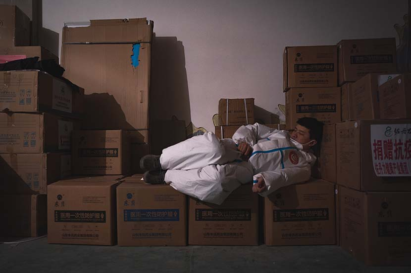 A volunteer naps atop boxes of protective gear in Tonghua, Jilin province, Feb. 2, 2021. Pan Yi for Sixth Tone