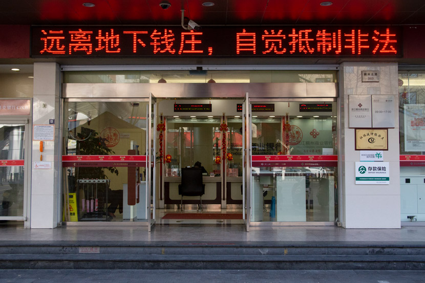 "The exterior view of a bank in Yiwu, Zhejiang province, March 14, 2021. The banner above the door reads: ""Stay away from underground banks, resist illegal foreign exchange."" Wu Peiyue/Sixth Tone"