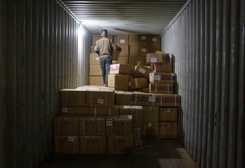 A worker stacks packages at a warehouse in Yiwu, Zhejiang province, March 14, 2021. Wu Peiyue/Sixth Tone