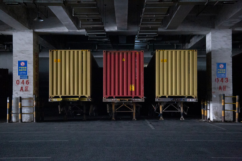 Containers are stacked inside a warehouse in Yiwu, Zhejiang province, March 14, 2021. Wu Peiyue/Sixth Tone