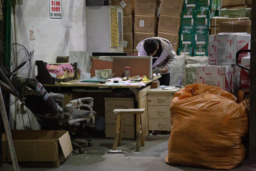 A worker checks shipping records at a warehouse in Yiwu, Zhejiang province, March 14, 2021. Wu Peiyue/Sixth Tone