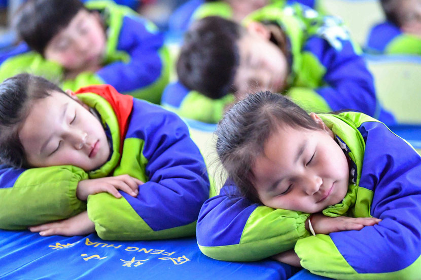 Students take an after-lunch nap a primary school in Bozhou, Anhui province, 2018. Liu Qinli/People Visual