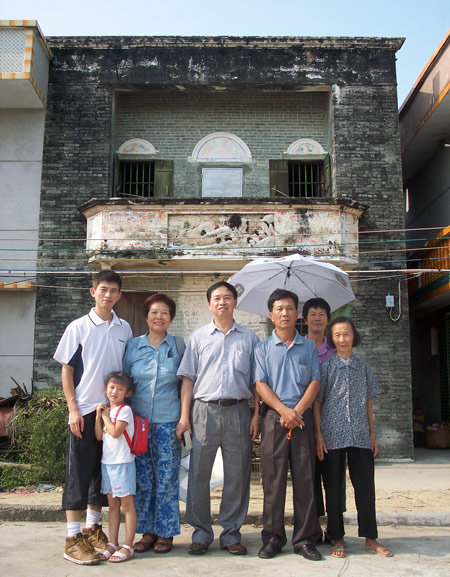 Huang Zhuocai (center) and his family pose for a photo in front of the house Huang Baoshi built in 1937. Courtesy of Huang Zhuocai