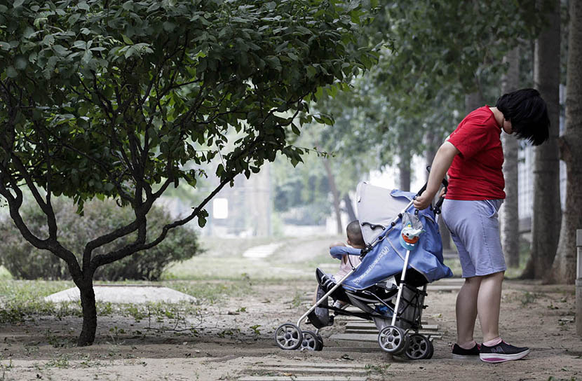 Sisi takes a stroll with her baby girl at a park in Beijing, June 7, 2016. Han Meng/Sixth Tone