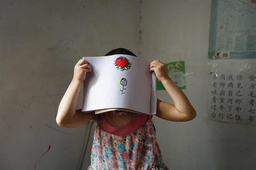 A young sexual abuse survivor holds up a drawing at her home in Pingdingshan, Henan province, May 13, 2014. VCG