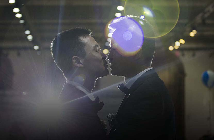 Sun Wenlin (left) and his partner Hu Mingliang lean in to kiss each other during their ceremonial wedding in Changsha, Hunan province, May 17, 2016. Wu Yue/Sixth Tone