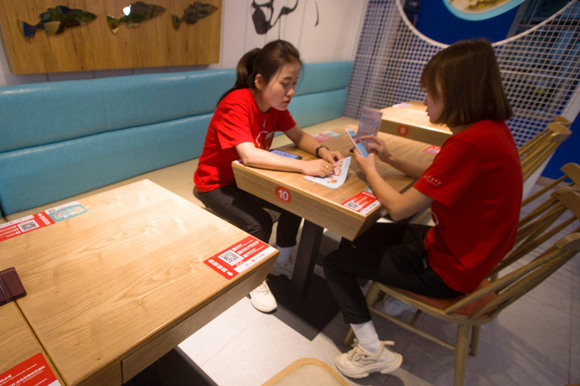 Two women order food with their phones at a restaurant in Taiyuan, Shanxi province, 2018. Zhang Yun/CNS/People Visual