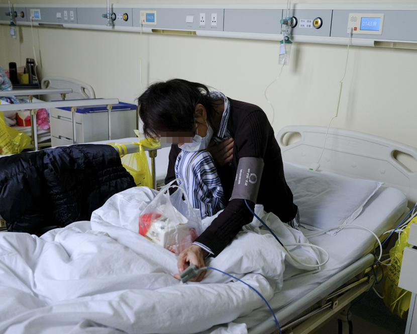 Guo Yin sits up in a ward inside the western branch of Wuhan Union Hospital, in Wuhan, Hubei province, April 11, 2020. Shi Yangkun/Sixth Tone