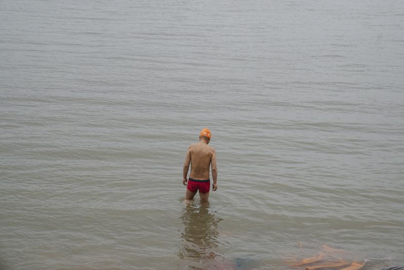 A swimmer wades into the Yangtze River, in Wuhan, Hubei province, April 2, 2021. Shi Yangkun/Sixth Tone