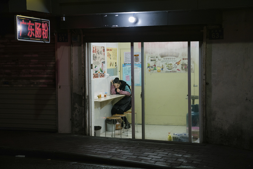 A waiter sits in the corner of a restaurant in Wuhan, Hubei province, April 2, 2021. Shi Yangkun/Sixth Tone