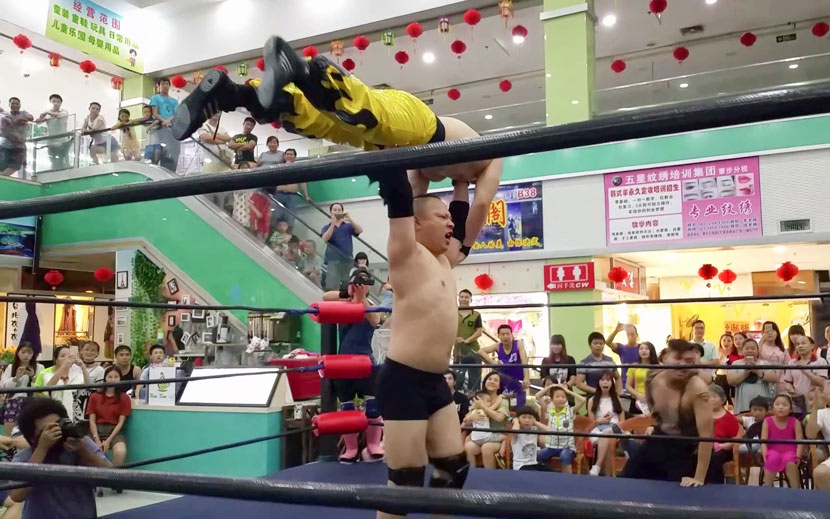 """Liu """"The Slam"""" Xuanzheng, founder of China Wrestling Entertainment, China's first pro wrestling group, lifts up his opponent during a show at a mall in Dongguan, Guangdong province, 2016. Courtesy of Liu Xuanzheng"""