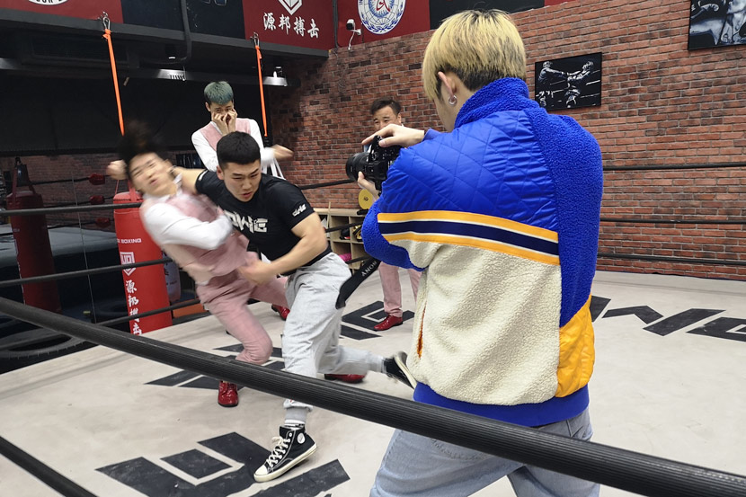"""Zhao Junjie is filmed pretending to beat up a group of """"little fresh meat"""" boy band members played by other OWE fighters for a TikTok video, in downtown Shanghai, March 5, 2021. Kenrick Davis/Sixth Tone"""