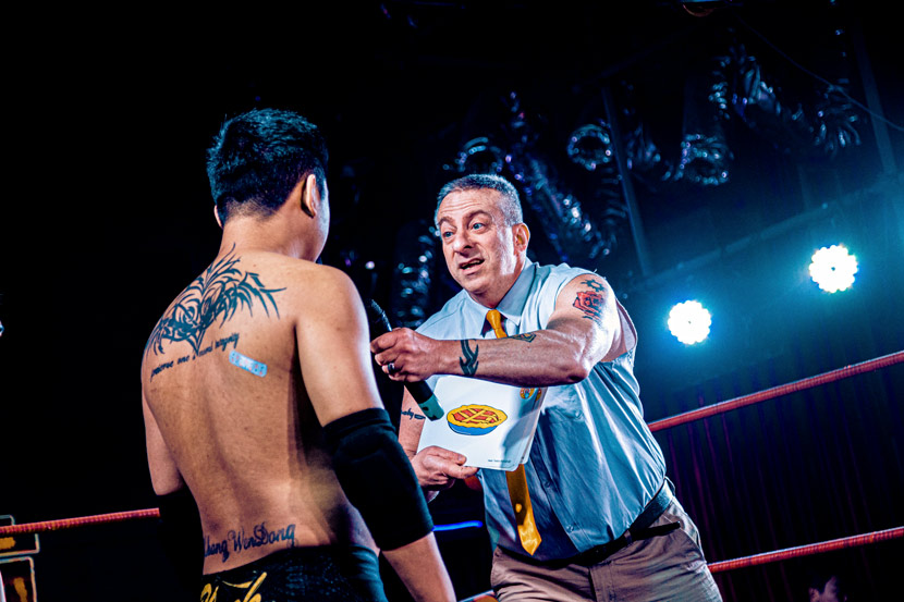 """Steve the ESL Teacher tests another fighter's English during an episode of Middle Kingdom Wrestling's show """"Blast-off!"""", recorded in Harbin, Heilongjiang province, 2020. Courtesy of MKW"""