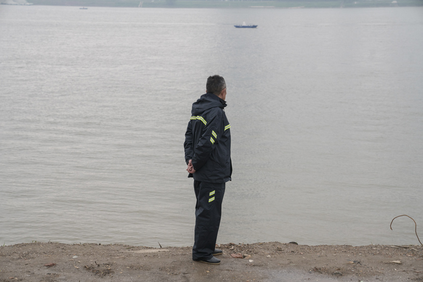 A man stands on the river bank in Wuhan, Hubei province, April 3, 2021. Shi Yangkun/Sixth Tone