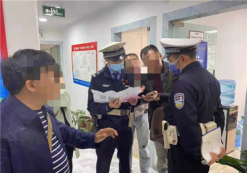 Officers speak with Yang, the father upset that his son's math exam score didn't improve more after expensive cram school classes, at a police station in Chongqing, April 20, 2021. From Weibo