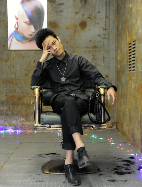 Luo Fuxing poses for a photo inside his now-closed hair salon in Shenzhen, Guangdong province, Dec. 22, 2017. Ge Yufei/People Visual
