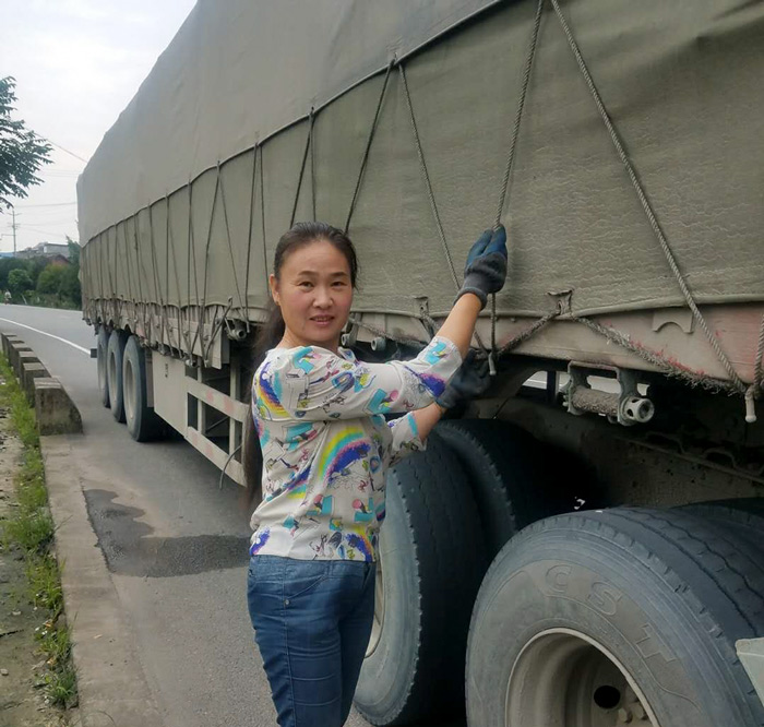 Miao Huiling tightens ropes along the truck. Courtesy of Transfar Harbour