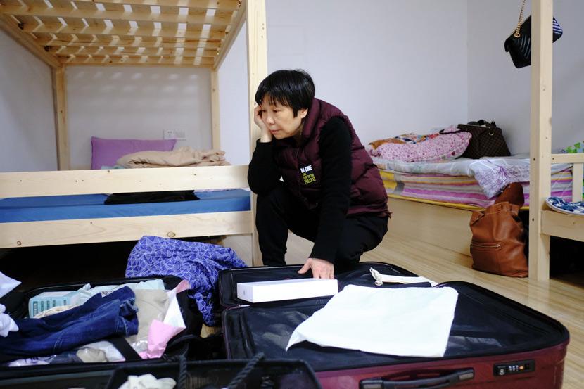 Shang Yao unpacks her son's belongings at Home of the Stars, in Jinzhai County, Anhui province, March 2021. Wu Huiyuan/Sixth Tone